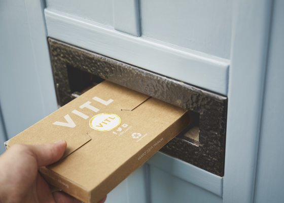 Man posting pack of VITL through letterbox